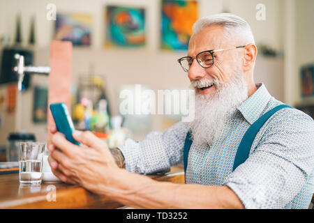 Hipster man using mobile phone while sitting in a bar - Senior male watching on new trends smartphone apps for social media - Stock Image