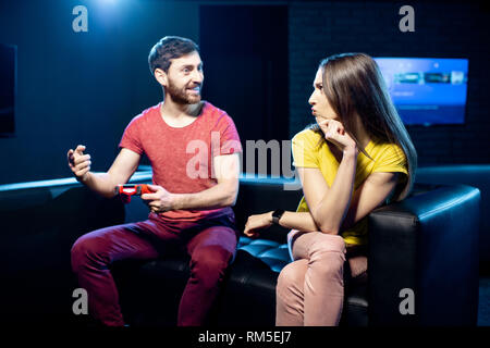 Woman offended by a boyfriend playing video games with gaming console sitting on the couch in the dark playing room - Stock Image