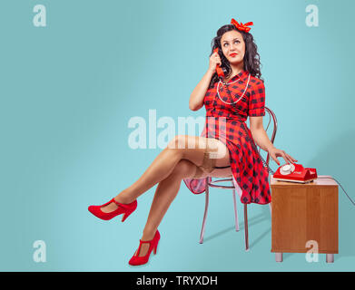 happy young pinup woman in red dress and nylon stockings sitting on a chair and talking on phone over green background - Stock Image
