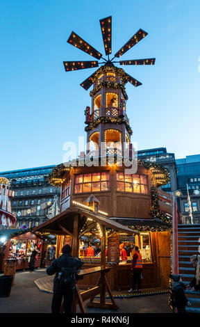 Large windmill with nativity figures and a Christmas Market stall selling hot sausage-based foods. George Square, Glasgow, Scotland, UK. People and st - Stock Image