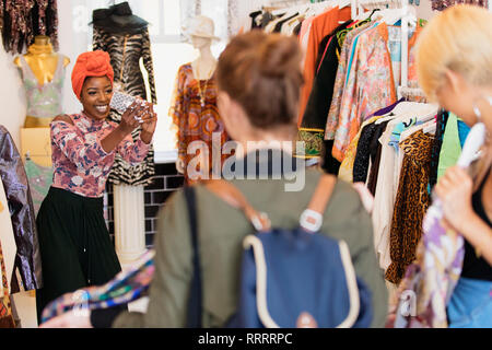 Young woman with camera phone photographing friends shopping in clothing store - Stock Image