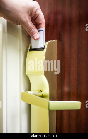 Hotel room door lock with a male person's hand inserting a key card to unlock the door - Stock Image