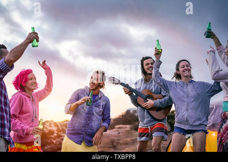 Happy friends making party at sunset while camping next the beach - Young people having fun dancing and drinking beer outdoor - Stock Image