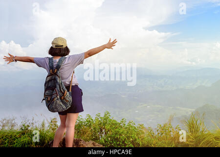Happy teens girl hiker with backpack and cap open arms looking beautiful nature landscape on high mountain at viewpoint - Stock Image
