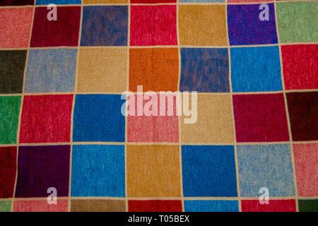 A multi coloured squared rug. - Stock Image