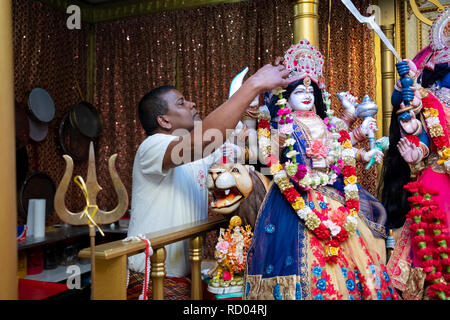 A devout Hindu worshipper decorate a statue of the goddess Durga with flowers. In Ozone Park, Queens, New York. - Stock Image