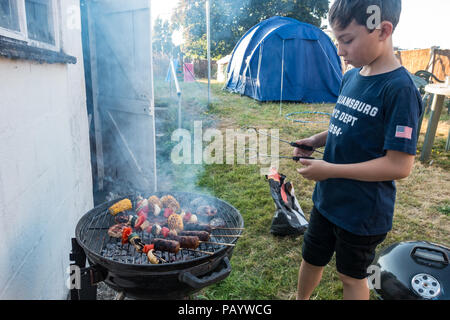 A young boy attends a barbecue in a back garden on which burgers, kebabs and vegetables are cooking. - Stock Image