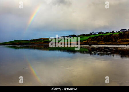 Ardara, County Donegal, Ireland. 20th December 2018. A rainbow briefly appears during stormy weather on the north-west coast. The rainbow is reflected on a wet sandy beach at Ballyganney. Credit: Richard Wayman/Alamy Live News - Stock Image