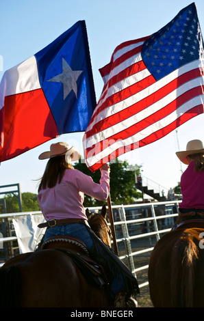 Cowgirls waving flag in stockyard on opening ceremony of PRCA rodeo event in Texas, USA - Stock Image