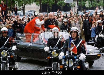 Pope John Paul II during his historic visit to Paris in 1980 travels in motorcade with light minimal security of open top car with police escort motorcycle outriders - Stock Image