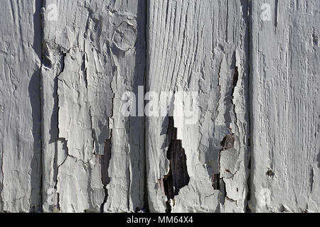 A closeup photo of an exterior of a wooden wall with some vertical lines and cracked old paint. - Stock Image