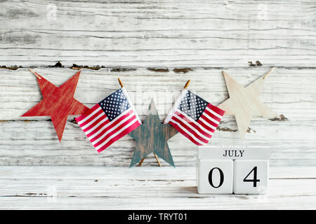 Fourth of July Background. Wood calendar blocks with the date July 4th to mark America's Independence Day. American flags with a star shaped banner ha - Stock Image