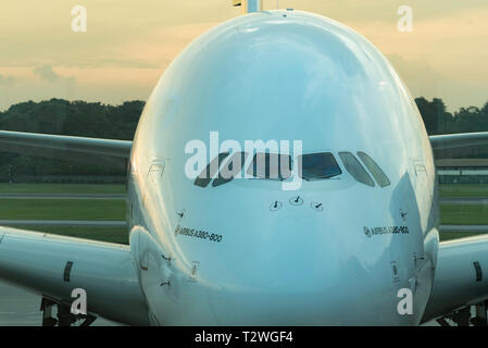 An Airbus A380 airplane parked at Singapore airport as the sun goes down behind it. - Stock Image