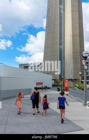 Woman mother and three female children daughters walking toward the CN Tower (base of Tower visible); visiting sightseeing Toronto on a sunny day. - Stock Image
