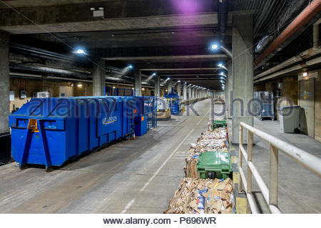 The service road for deliveries beneath a UK shopping mall, a blue compactor and bales of crushed cardboard for recycling. - Stock Image