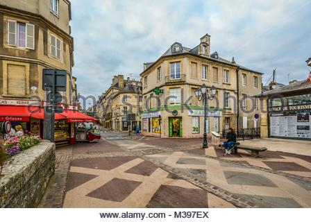 The one way Rue Saint-Jean, the main street full of cafes and shops in the Normandy city of Bayeux, France with - Stock Image