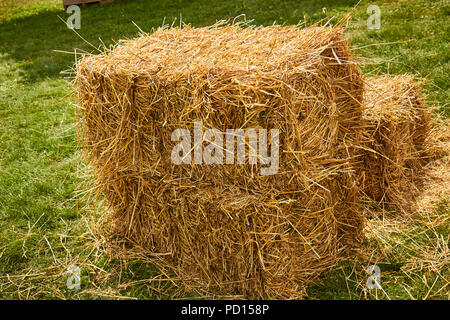 A square hay bale made from antique farm machinery - Stock Image