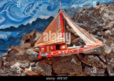 A small colourful decorative yacht part of an elaborate external house wall decoration in El Cotillo, on Fuerteventura, - Stock Image