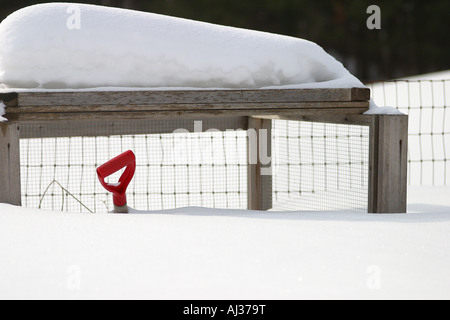 Snow shovel with a red handle buried under lots of snow - Stock Image