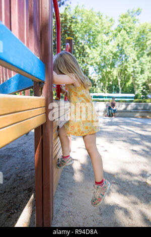 Three years old blonde girl with yellow dress playing to climb on wooden construction in outdoor playground, with mother woman watching, in public par - Stock Image