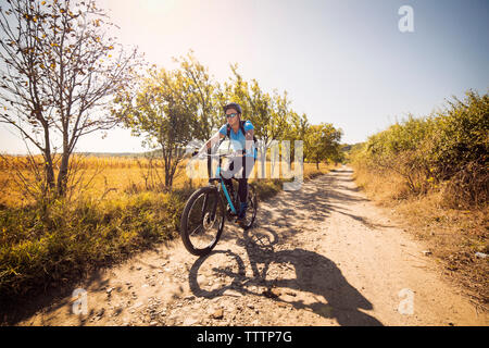 Man cycling on dirt road against clear sky - Stock Image