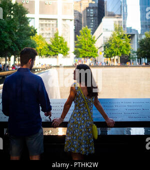 A young couple in conversation while paying their respects at the 9/11 World Trade Centre Memorial fountains in Lower Manhattan, New York City - Stock Image
