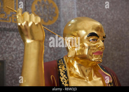 Detail of Gilt Lohan Arhat cleaning his ears with stick inside Kuang Im Chapel, near River Kwai, Kanchanaburi, Thailand. - Stock Image