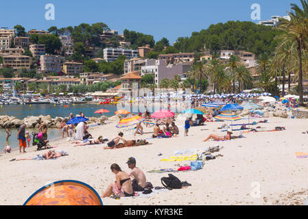 People relaxing on the beach on a warm summer`s day in Port De Soller, Mallorca, Spain. - Stock Image