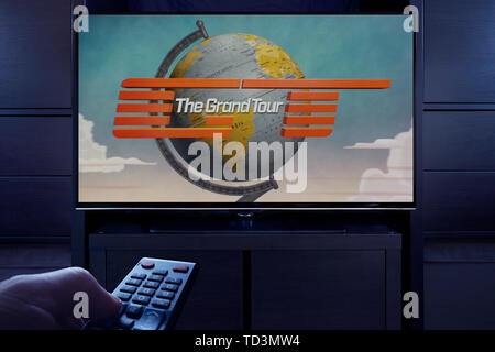A man points a TV remote at the television which displays The Grand Tour main title screen (Editorial use only). - Stock Image