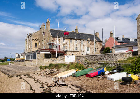 Upturned boats on seashore by Findhorn House built in 1775 home of Royal Findhorn Yacht Club overlooking Findhorn Bay. Findhorn, Moray, Scotland, UK, - Stock Image