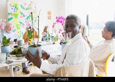 Portrait confident active senior man enjoying flower arranging class - Stock Image