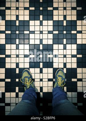 Selfportrait of feet above vintage tiles - Stock Image