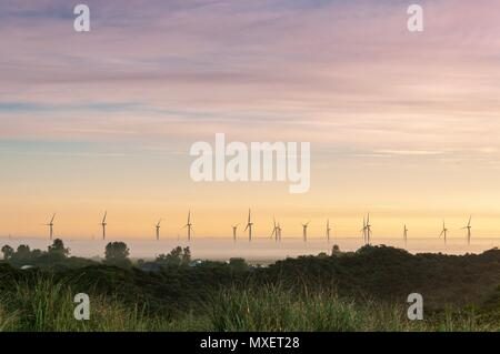 Wind turbines rising out of the mist at sunrise on a summer's morning - Stock Image