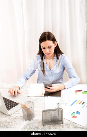 Businesswoman sending sms meanwhile working at the office - Stock Image