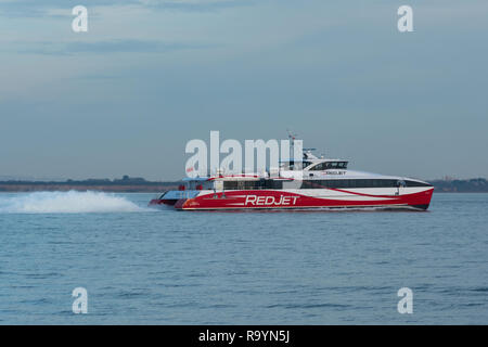 Red jet hi-speed catamaran ferry crossing the Solent between Southampton and West Cowes on the Isle of Wight - Stock Image