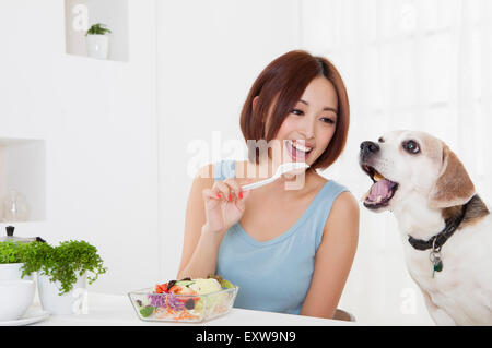 Young woman looking at dog with smile, - Stock Image
