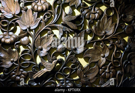Ornate brown Buddhist wood hand carvings with a Thai theme grain and texture often seen in home restaurant decorations - Stock Image