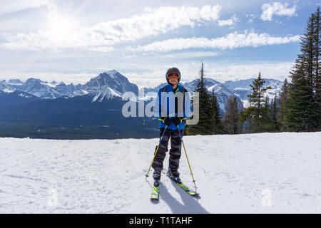 Young skier standing at the edge of a mountain range in sunny Lake Louise at the Canadian Rockies of Alberta, Canada. - Stock Image