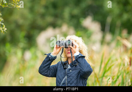 Rainham Marshes Essex UK - mature woman middle aged birdwatching with binoculars - Stock Image