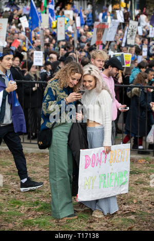 Two female protestors checking phone at People's Vote March, London, England - Stock Image