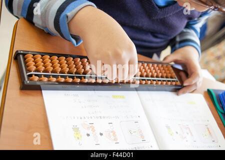 Child using abacus studying math - Stock Image