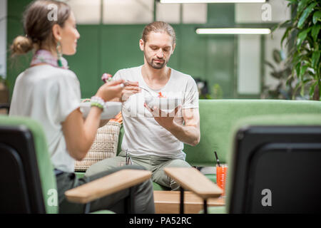 Vegetarian couple eating healthy salads sitting together on the sofa at the beautiful green interior - Stock Image