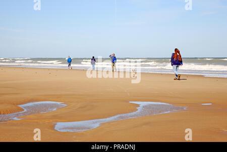 Beach walkers on the shoreline in North Norfolk at East Runton, Norfolk, England, United Kingdom, Europe. - Stock Image
