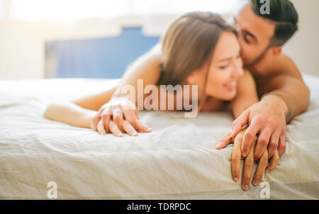 Young couple in love kissing and having sex in the bed - Passionate lovers having romantic and intimate moments in the bedroom - Stock Image