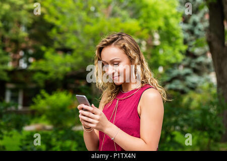 A beautiful young woman texting on her smart phone outside on a university campus; Edmonton, Alberta, Canada - Stock Image