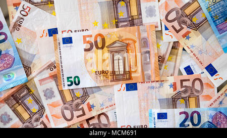 Background of lots of Euro banknotes of different denominations, with focus on the 50 euros, spread on a surface, concept for poor and wealthy - Stock Image
