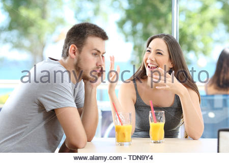 Bored man listening her friend talking in a coffee shop or hotel on the beach - Stock Image