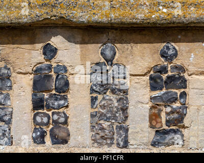 Details of knapped flint and stone church walls - Stock Image