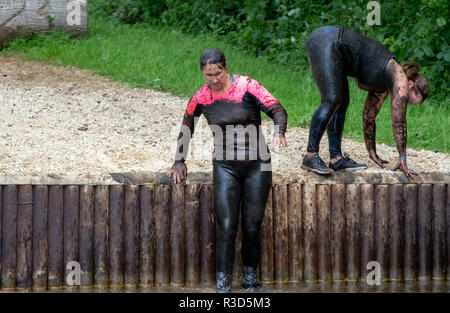 Rather soiled lady mud runners around a water crossing - Stock Image
