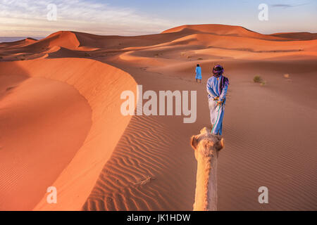 Two nomadic tribesmen wearing traditional clothing lead a camel through the Sahara Desert in Morocco. - Stock Image